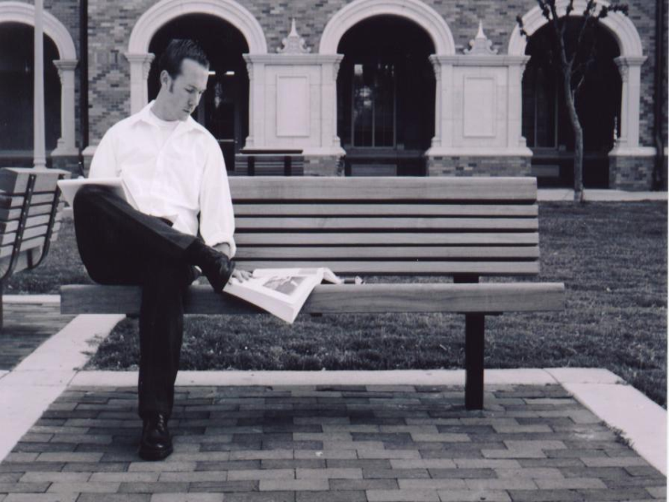 man sitting on bench reading newspaper