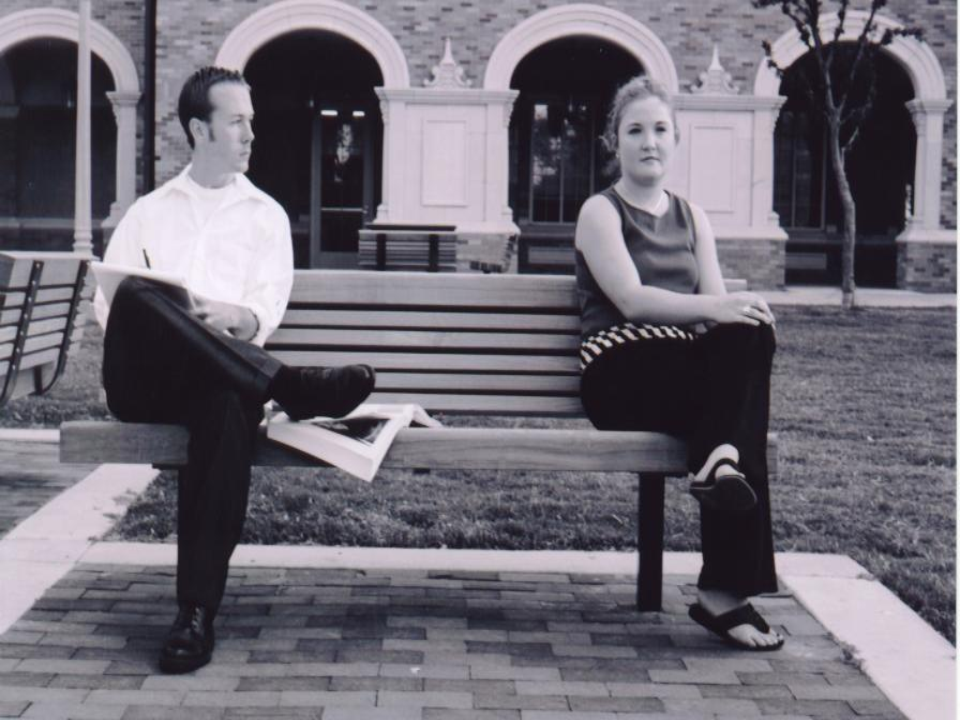 women sits down on a bench next to man